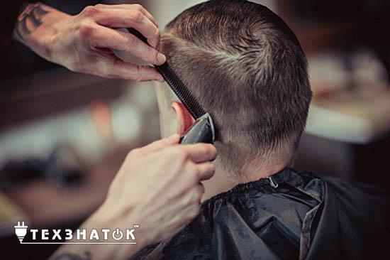 парикмахер стрижет мужчину