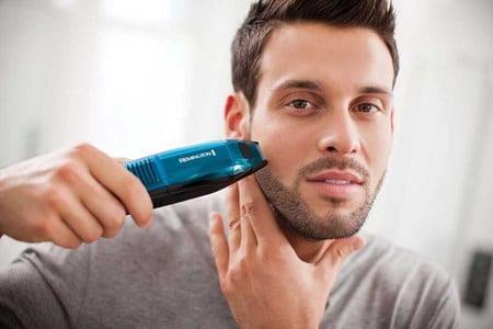 Мужчина ровняет бороду триммером