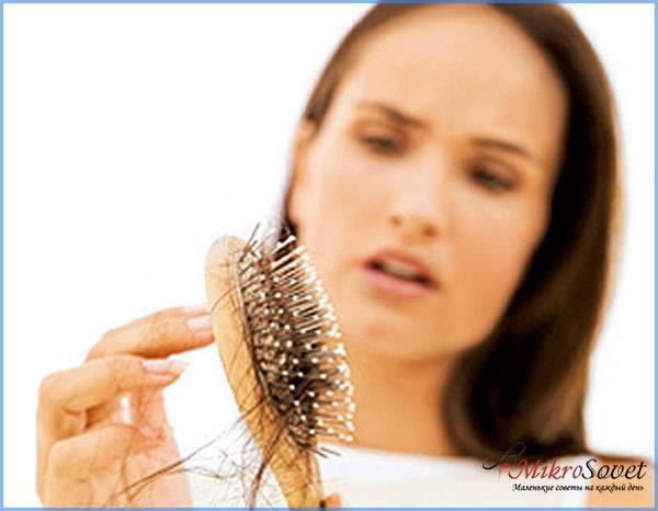 девушка держит расческу с выпавшими волосами