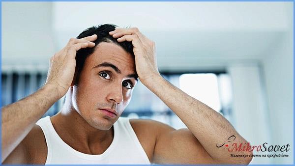 мужчина брюнет трогает свои волосы