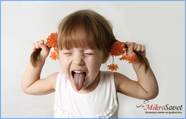 маленькая девочка тянет себя за волосы и показывает язык