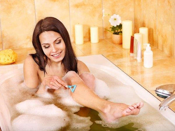 Девушка бреет ноги в ванной.