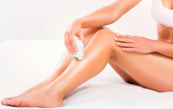 Девушка бреет ноги эпилятором.
