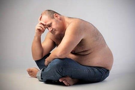 Мужчина с лишним весом сидит