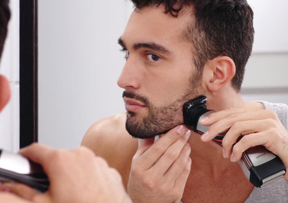 мужчина бреется триммером
