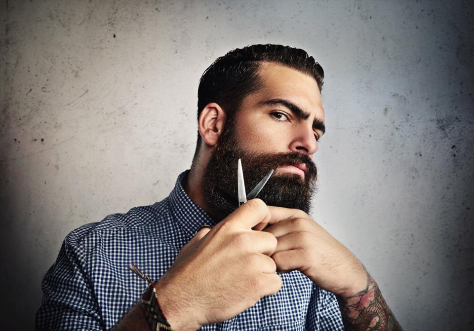 мужчина стрижет бороду ножницами