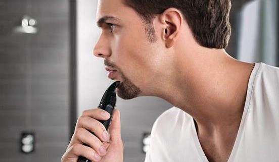 Мужчина стрижет триммером бороду