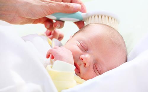 Почти лысого новорожденного осторожно причёсывают щёткой