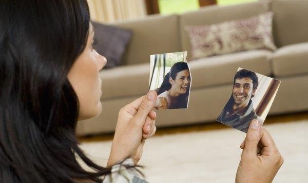 Девушка смотрит на разорванное фото.