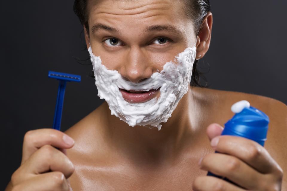 мужчина держит в руках бритвенный станок и пену для бритья